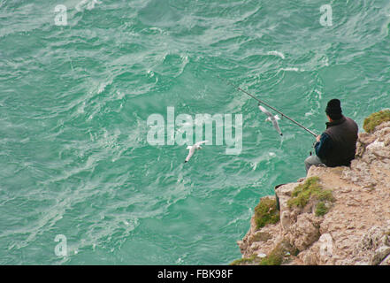 Severe dramatic seascape with fisherman in Cape Saint Vicent cliffs, Portugal - Stock Photo