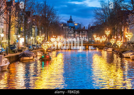 Amsterdam Herengracht Canal in winter with seasonal lights and small boat at dusk. Amsterdam Light Festival - Stock Photo