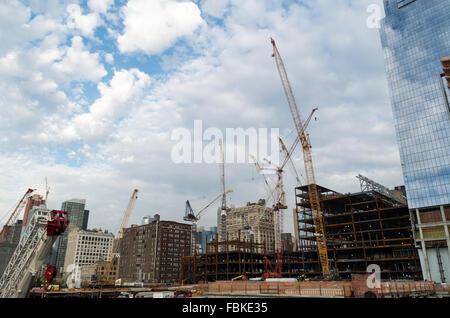 Multiple cranes and heavy lifting machinery on a construction site in Chelsea, New York City, as new skyscrapers - Stock Photo
