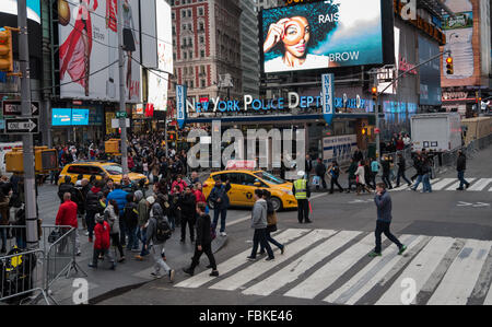 Crowds of people outside the NYPD station, the only one to have a neon sign, in Times Square New York City. - Stock Photo