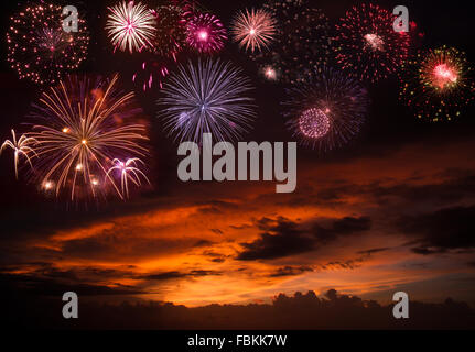 Holiday fireworks in sunset sky - Stock Photo