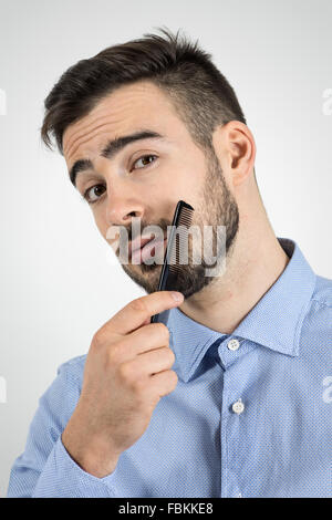 Close up portrait of young bearded man combing his beard looking at camera. Desaturated portrait over gray studio - Stock Photo
