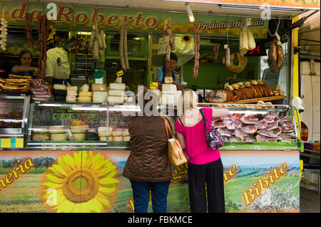A stall selling cheeses, salami, sausages and porchetta at the weekly market, Siena, Tuscany, Italy - Stock Photo
