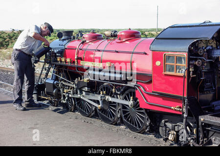 England, Kent, Dungeness. The driver tops up the oil levels in the miniature steam locomotive, 'Winston Churchill'. - Stock Photo
