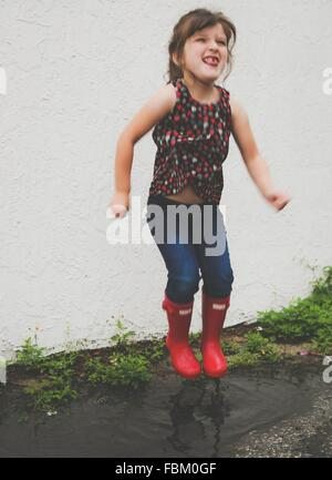 Young Girl Jumping In Puddle Wearing Wellies - Stock Photo