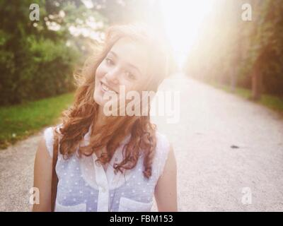 Portrait Of A Smiling Young Woman On Country Road - Stock Photo