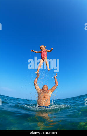 Grandfather tossing up the high air with water splashes joyful baby girl on sea beach. Outdoors child activity, - Stock Photo
