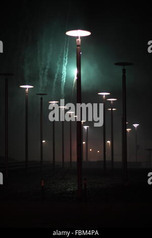 Illuminated Street Lights Against Firework In Sky At Night - Stock Photo