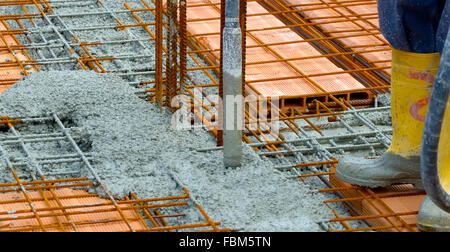 Construction worker compacting liquid cement in reinforcement form work during concreting floors pouring works - Stock Photo