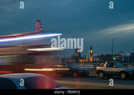 Big Ben Houses of Parliament and London Eye view from Waterloo Bridge at night with moving London bus - Stock Photo