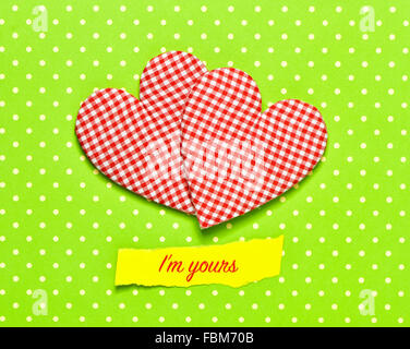 two red and white checkered hearts and the text I am yours on a colorful green dot-patterned background - Stock Photo