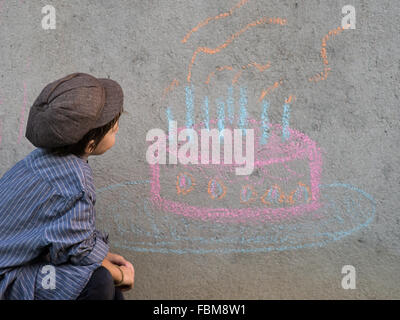 Boy drawing birthday cake on wall with chalk - Stock Photo