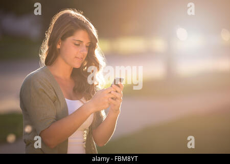 Girl texting on smart phone - Stock Photo