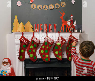 Boy standing in front of fireplace pointing at christmas stockings and decorations - Stock Photo