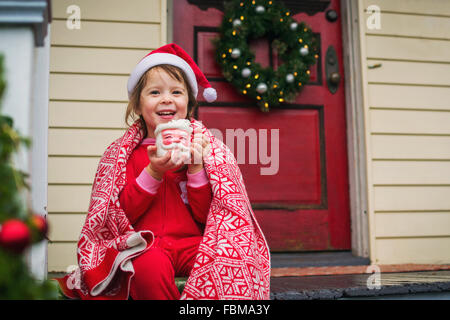 Girl sitting on front porch drinking hot cocoa in Santa mug - Stock Photo