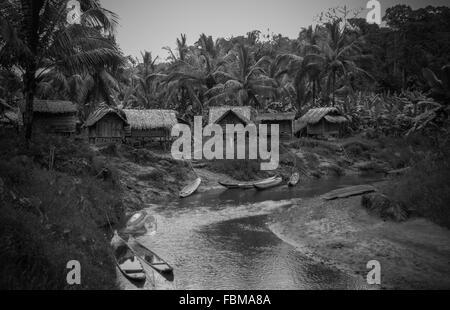 Countryside Houses Against Trees With Lake In Foreground - Stock Photo