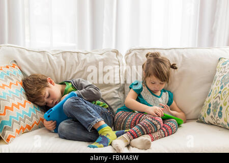 Boy and girl lying on couch playing with digital tablets - Stock Photo