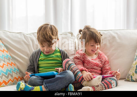 Boy and girl sitting on couch playing with digital tablets - Stock Photo