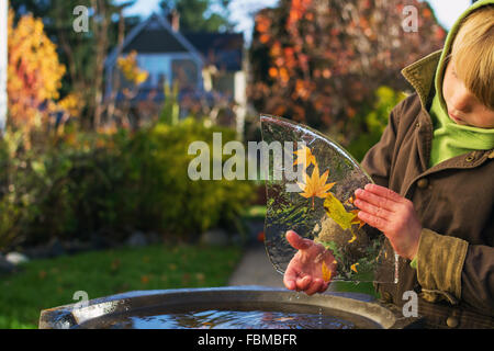 Young boy outside holding leaves frozen in ice - Stock Photo