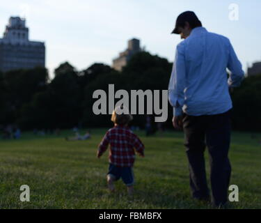Rear View Of Father And Son Walking On Landscape - Stock Photo