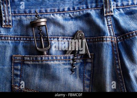 Old corkscrew, bottle opener in the pocket of jeans - Stock Photo