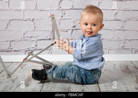 Child playing with wooden meter stick - Stock Photo