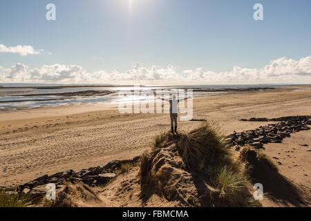 Man with arms outstretched standing on sand dune at the beach - Stock Photo