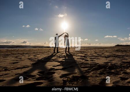Silhouette of a couple dancing on the beach - Stock Photo