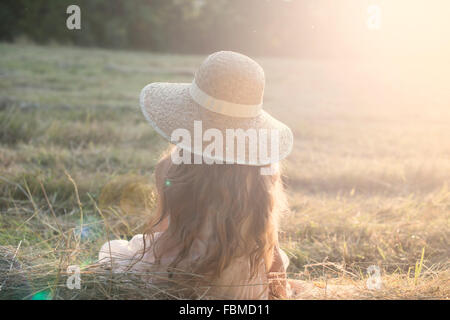Rear view of a girl sitting in a field - Stock Photo