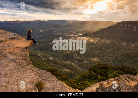 Woman sitting on mountain ledge, Blue Mountains National Park, New South Wales, Australia - Stock Photo
