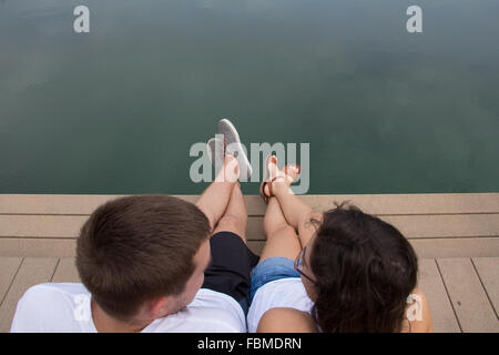 Young Couple sitting by waterfront - Stock Photo