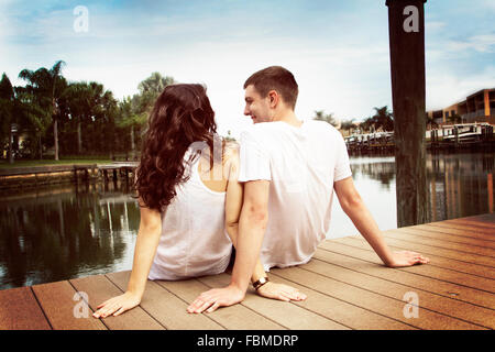 Rear view of a couple sitting on jetty - Stock Photo