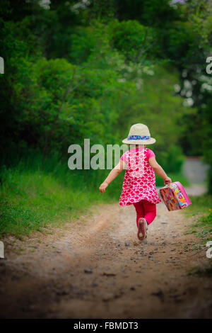 Girl running along footpath in forest - Stock Photo