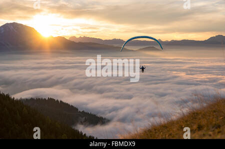 Paraglider flying above the Clouds, Salzburg, Austria - Stock Photo