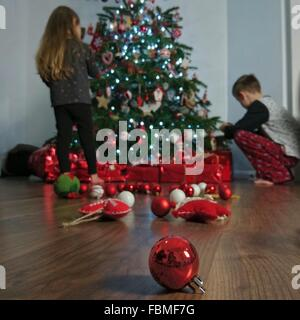 Boy and girl decorating Christmas tree - Stock Photo