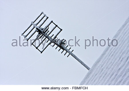 A television aerial on a snow-covered roof - Stock Photo