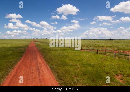 Brazilian landscape with a long straight country road showing red earth, near Bonito, Mato Grosso do Sul, Brazil - Stock Photo