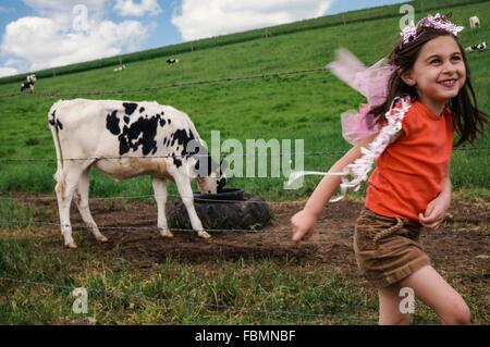 Happy Girl Walking While Calf Grazing In Background On Field - Stock Photo