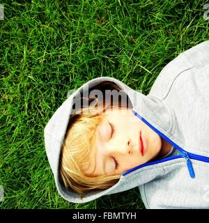 Directly Above Shot Of Boy Relaxing On Grassy Field In Park - Stock Photo
