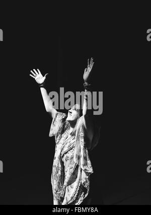 Young Woman Raising Hands Over Black Background - Stock Photo
