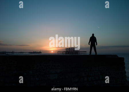 Man standing on groyne, silhouette, sunrise - Stock Photo