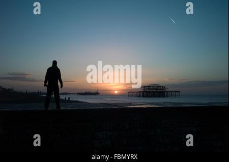 Man standing on groyne, silhouette, sunrise - Stock Photo