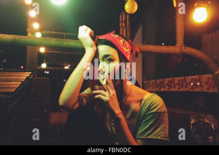 Young Woman With Head In Hand Smoking While Sitting In Illuminated Balcony - Stock Photo