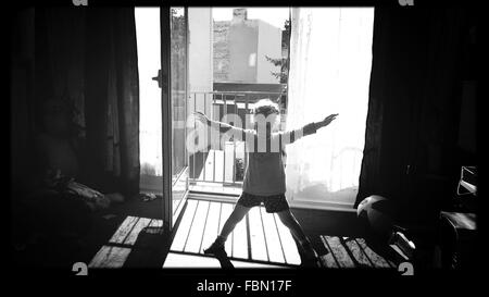 Full Length Of Girl With Arms Outstretched And Legs Apart At Home - Stock Photo