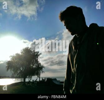 Low Angle View Of Young Man Standing Against Sky - Stock Photo