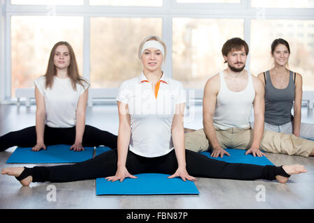 Fitness, stretching practice, group of four beautiful happy fit young people working out in sports club, doing easy - Stock Photo