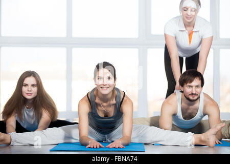 Fitness, stretching practice, group of three beautiful happy fit young people working out in sports club, doing - Stock Photo
