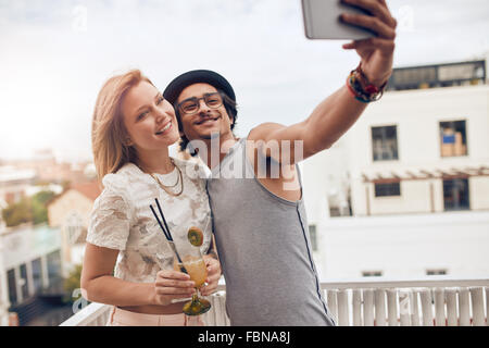 Couple of friends having a party on the rooftop taking a selfie with woman drinking cocktail. They are happy and - Stock Photo