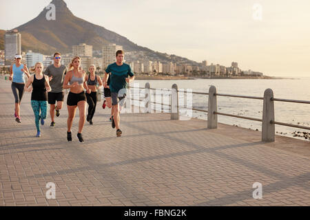 Healthy young people running along the seaside. Running club group training together on a walkway by the sea in - Stock Photo