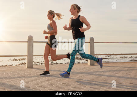 Two young women running along a seaside promenade. Fit young runners working out together on a road by the sea. - Stock Photo